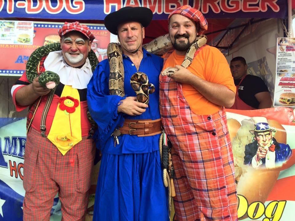 Boldog István (Fidesz) betyárruhában, egy kígyóval a nyakában, bohócokkal