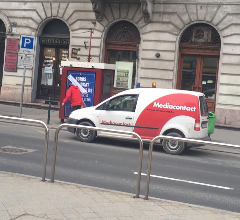 """Neoreneszánsz festmény: egy offshore tulajdonú köztéri reklámcég alkalmazottja a """"Goebbels likes this"""" feliratot kaparja le a kormány sorosozós reklámjáról Budapesten"""