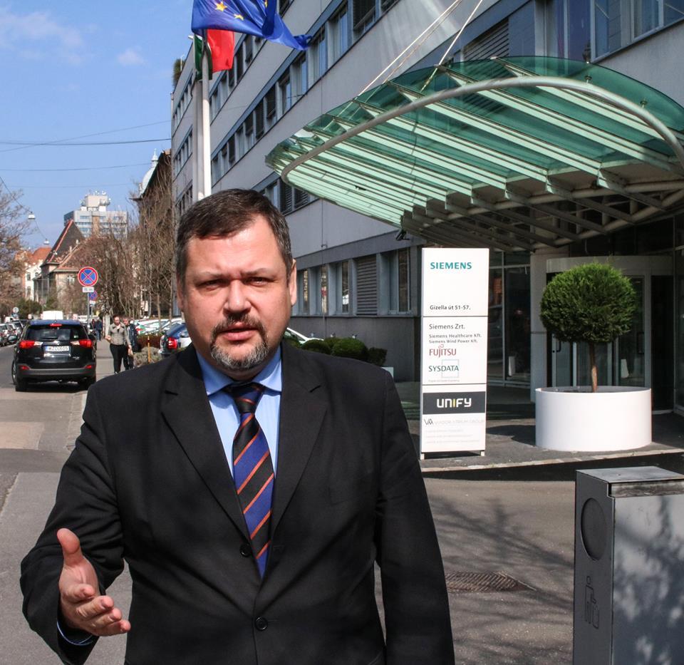 A Fidesz zuglói jelöltje azzal állt ki a Siemens irodája elé, hogy a Soros-hálózat a céget felhasználva akarja zsarolni az országot