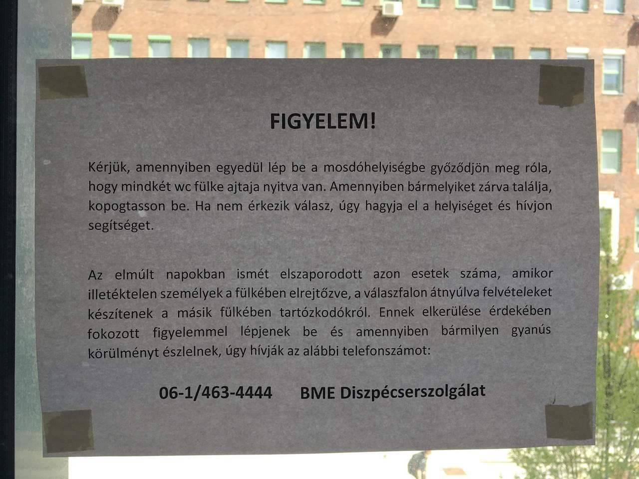 """A BME """"E"""" épületében felirat figyelmeztet, hogy vigyázz, mert a szomszédos vécéfülkéből átnyúlva felvehetnek"""