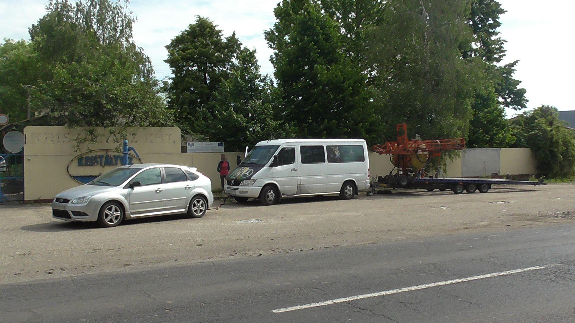 Egy román sofőr Mátészalkán megmutatta, hogyan lehet egyszerre kisbuszt és trélerre kötözött permetezőt vontatni