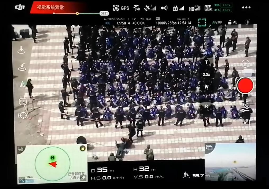 Kiszivárgott drónvideón látszik, amint Kínában több száz kopaszra nyírt, bekötött szemű, hátrakötött kezű embert ültetnek a földre egy vonat mellett