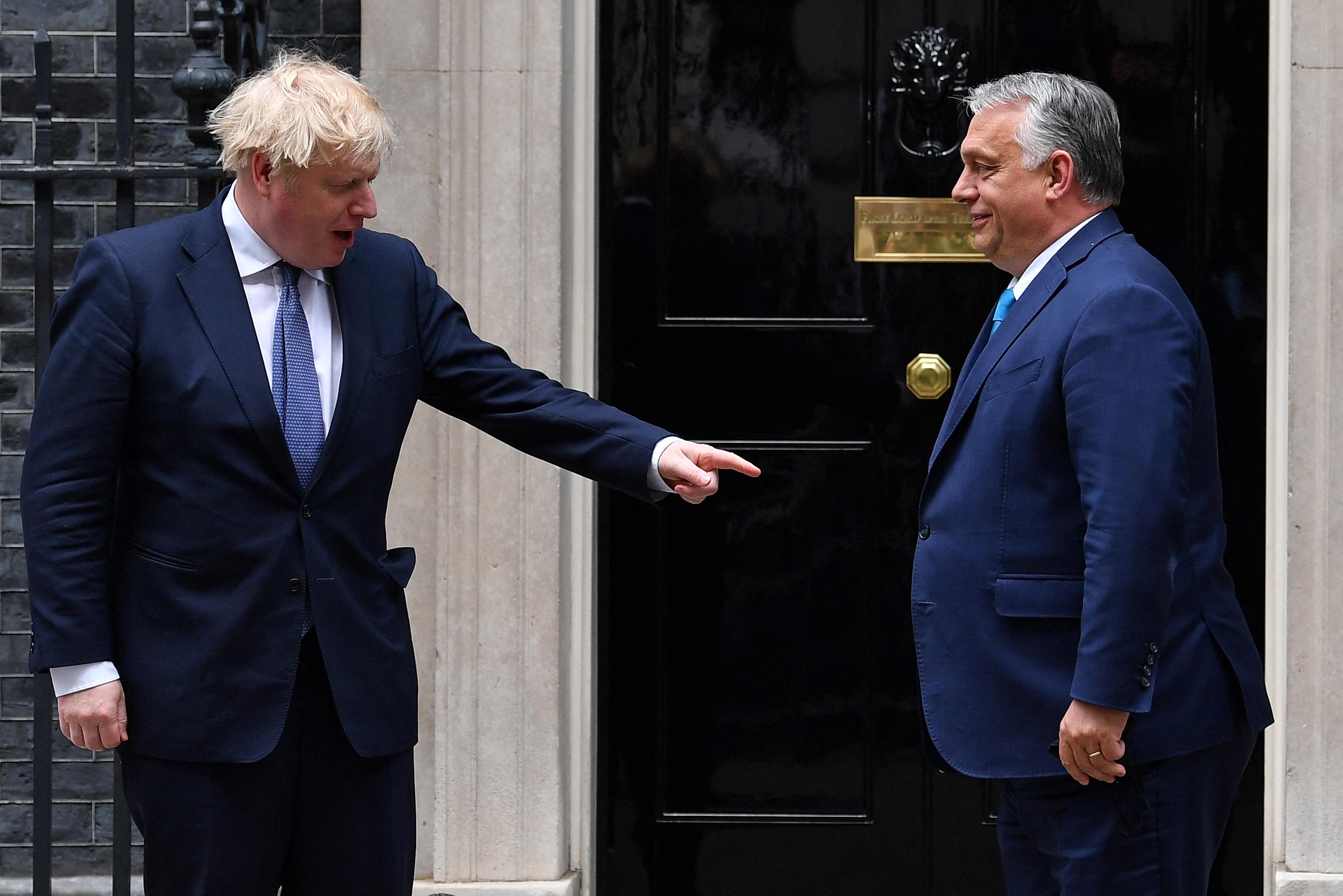 Egy kép, amin Boris Johnson Orbán Viktor bendőjére mutat