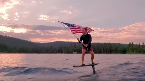 Mark Zuckerberg egy amerikai zászlóval egy elektromos szörfdeszkán a Take me home, Country Roadsra szeli a habokat